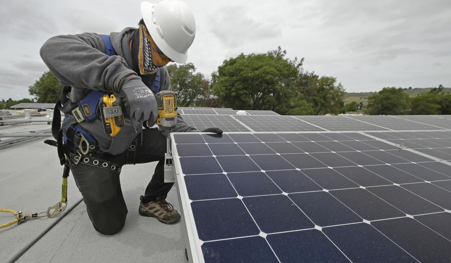 Gen Nashimoto, of Luminalt, installs solar panels in Hayward, Calif., on Wednesday, April 29, 2020. From New York to California, the U.S renewable energy industry is reeling from the new coronavirus pandemic, which has delayed construction and sowed doubts about major projects on the drawing board. (AP Photo/Ben Margot)