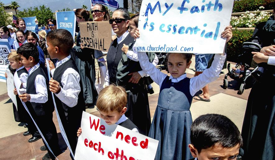 Young members of the Church of God hold signs during a demonstration against California's stay-at-home orders that were put in place due to the coronavirus outbreak, in Rancho Cucamonga, Calif., Sunday, May 3, 2020. (Watchara Phomicinda/The Orange County Register via AP)