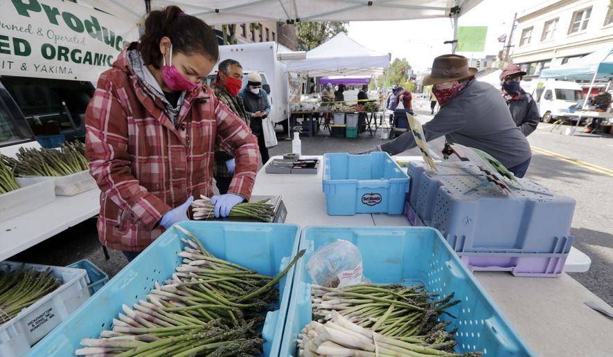 Farmer Alegria Canales stacks asparagus as a customer behind completes his purchase at her family's stand in the West Seattle Farmers Market during its first opening in nearly two months because of the coronavirus outbreak Sunday, May 3, 2020, in Seattle. (AP Photo/Elaine Thompson)  **FILE**