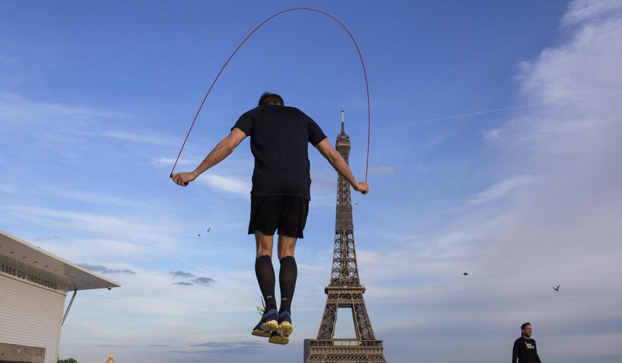 A man exercises along Trocadero Square, close to the Eiffel Tower, Saturday, May 2, 2020, in Paris. France continues to be under an extended stay-at-home order until May 11 in an attempt to slow the spread of the coronavirus pandemic. (AP Photo/Rafael Yahgobzadeh)