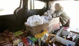 """Lynn Ehmen carries supplies to the micro food pantry at Lanphier High School in Springfield as Kristina Moss arrives to drop off supplies, too, Saturday, April 18, 2020. The pantries """"take what you want, leave what you can,"""" encourages those with extra to help those who are in need. (Ted Schurter/The State Journal-Register via AP)"""
