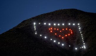A Nevada light display on Black Mountain shines Wednesday, April 22, 2020, in Henderson, Nev. Las Vegas attorney David Koch and his 18-year-old son, Mason, hiked up the mountain April 17 to place the lights as a show of support for their community amid the response to the coronavirus. (L.E. Baskow/Las Vegas Review-Journal via AP)