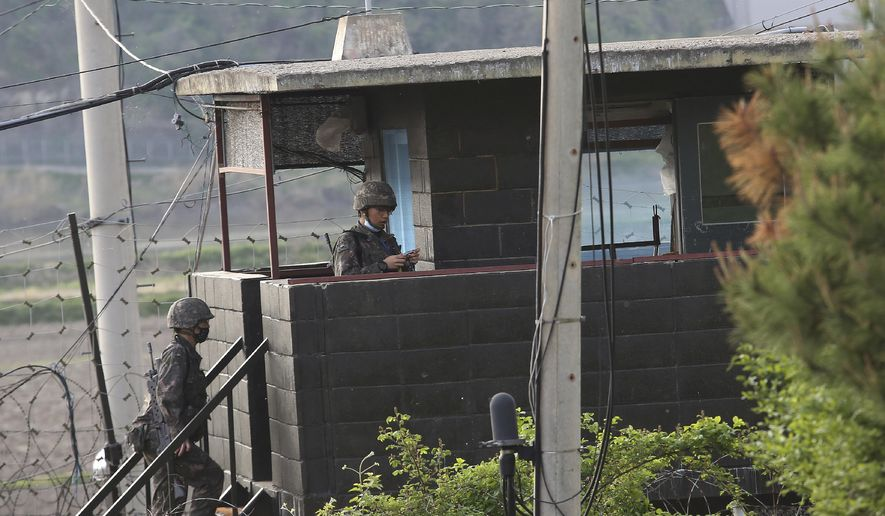 Army soldiers walk up the stairs of their military guard post in Paju, South Korea, near the border with North Korea, Sunday, May 3, 2020. North and South Korean troops exchanged fire along their tense border on Sunday, the South's military said, blaming North Korean soldiers for targeting a guard post. (AP Photo/Ahn Young-joon)