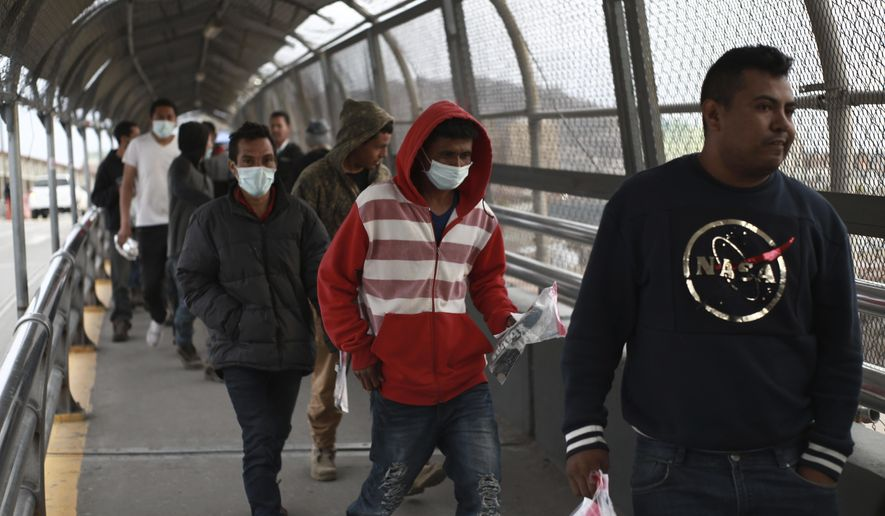 In this Saturday, March 21, 2020, file photo, Central American migrants seeking asylum, some wearing protective face masks, return to Mexico via the international bridge at the U.S-Mexico border that joins Ciudad Juarez and El Paso. Mexico and the U.S. are restricting travel over their busy shared border as they try to control the spread of the coronavirus pandemic. (AP Photo/Christian Chavez) ** FILE **