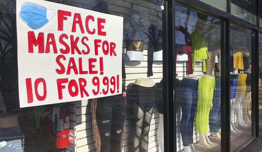 A women's boutique clothing store in the Bronzeville neighborhood of Chicago, advertises the selling of masks Sunday, May 3, 2020. (AP Photo/Charles Rex Arbogast)