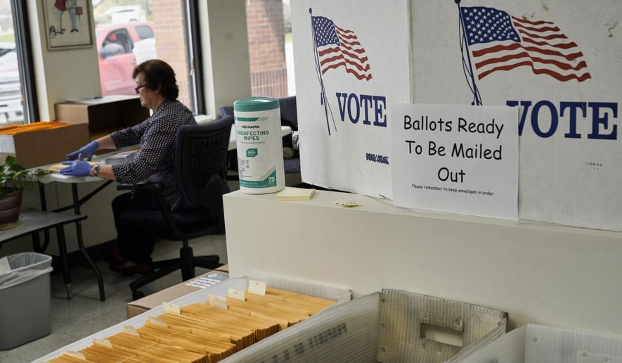 In this April 14, 2020 photo, mail-in ballots ready to be mailed are seen at the Lancaster County Election Committee offices in Lincoln, Neb. Officials in Nebraska are forging ahead with plans for the state's May 12 primary despite calls from Democrats to only offer voting by mail and concerns from public health officials that in-person voting will help the coronavirus spread.  Republican leaders have encouraged people to request absentee ballots but say polling places will be open.  (AP Photo/Nati Harnik)