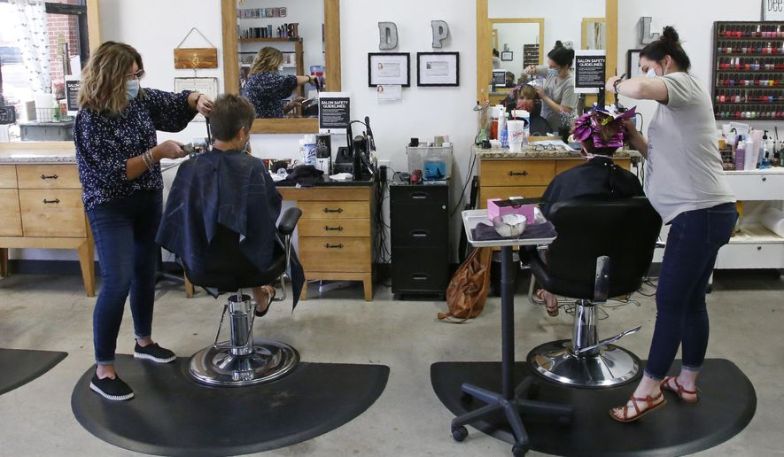 Denise Gavitt, left, and Lauren Matheson, right, attend to clients at Gavitt's salon, Beehive Salon, Friday, May 1, 2020, in Edmond, Okla., the first day hair salons have been allowed to reopen in Edmond following shutdowns due to coronavirus concerns. (AP Photo/Sue Ogrocki)
