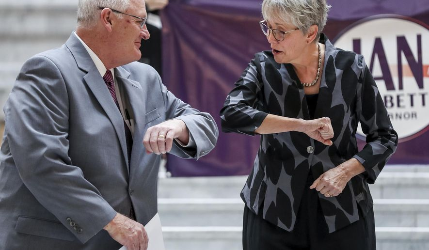 In this March 19, 2020, photo, Republican gubernatorial candidate Jan Garbett, right, elbow-bumps Dr. Joseph Jarvis as she introduces him as her running mate at the state Capitol in Salt Lake City. Social distancing rules, stay-home orders and mass gathering restrictions aimed at preventing the spread of the new coronavirus have made the crucial signature-gathering component of American electoral politics impossible. (Spenser Heaps/The Deseret News via AP)