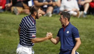 In this Sept. 28, 2018, file photo, Dustin Johnson left, and Rory McIlroy shake hands on 16th green at the end of a fourball match on the opening day of the 42nd Ryder Cup in Saint-Quentin-en-Yvelines, outside Paris, France. Johnson and McIlroy headline a $3 million charity match for COVID-19 relief that will mark the first live golf on television since the pandemic shut down sports worldwide. The May 17 match will be played at Seminole Golf Club in South Florida. (AP Photo/Alastair Grant, File)  **FILE**