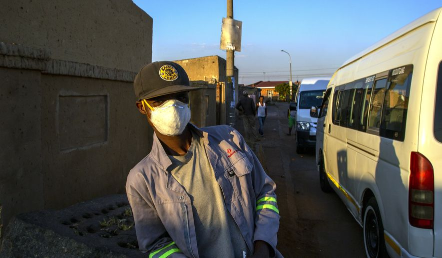 Senzo Mkhize, a taxi marshal, wearing protective face mask as a precaution against the spread of the new coronavirus, stands on a street in Thokoza township, east Johannesburg, South Africa, Monday, May 4, 2020, after the government lifted some of the restrictions placed on residents after a five-week lockdown in a bid to combat the spread of coronavirus. (AP Photo/Themba Hadebe)