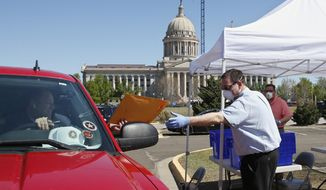 FILE - In this April 8, 2020 file photo, Paul Ziriax, right, secretary of the Oklahoma State Election Board, takes filing paperwork from state Sen. Paul Scott, left, R-Duncan, at a drive-thru registration area outside the state Capitol in Oklahoma City. The Oklahoma Supreme Court says mail-in absentee ballots cast by voters do not have to be notarized by a notary public to be valid. In a 6-3 opinion on Monday, May, 4, 2020, the high court wrote that a statement signed, dated and made under the penalty of perjury is adequate for submitting an absentee ballot by mail. (AP Photo/Sue Ogrocki, File)