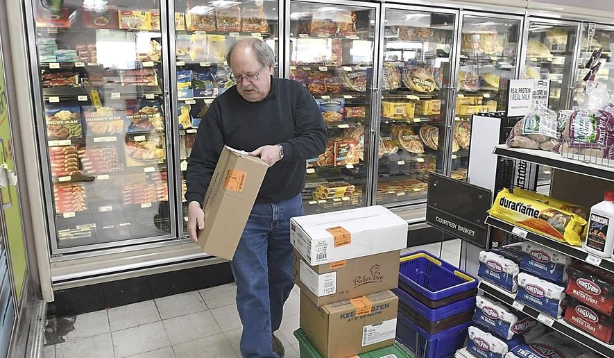 Michael Tatge, owner of The Market in Madison Lake, puts away frozen goods after a delivery Wednesday, April 22, 2020. Rural grocers are among those dealing with supply headaches during the pandemic. (Pat Christman/The Free Press via AP)