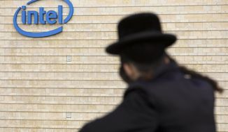 "FILE - In this Nov. 14, 2009 file photo, an ultra-Orthodox Jewish man is seen next to Intel's office building in Jerusalem. Intel said Monday, May 4, 2020, that it has purchased Israeli urban mobility startup Moovit for $900 million. The California-based chipmaker said the purchase buttresses its plan to become a ""complete mobility provider. (AP Photo/Bernat Armangue, File)"