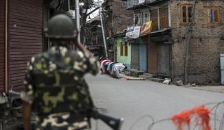 An Indian paramilitary soldier stands guard as Kashmiri Muslims offer Friday prayers on a street outside a local mosque during curfew like restrictions in Srinagar, India, Aug. 16, 2019. The image was part of a series of photographs by Associated Press photographers which won the 2020 Pulitzer Prize for Feature Photography. (AP Photo/Mukhtar Khan)