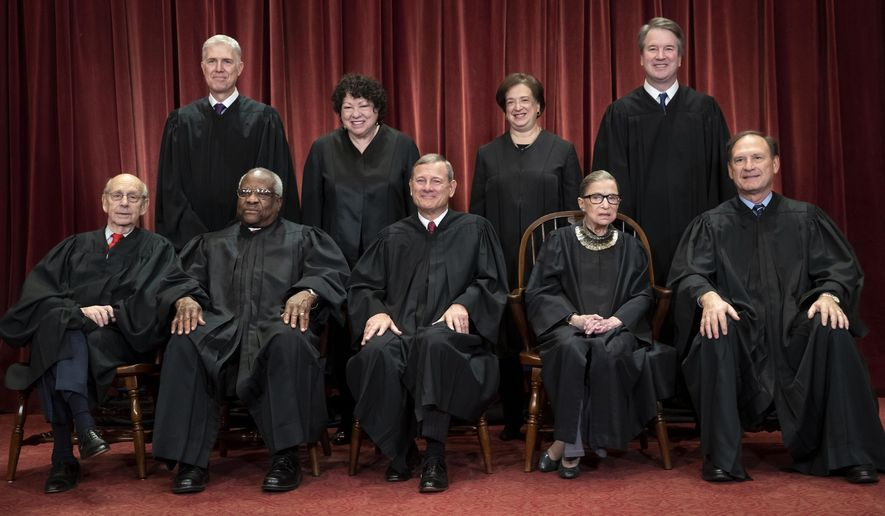 In this Nov. 30, 2018, file photo, the justices of the U.S. Supreme Court gather for a formal group portrait to include the new Associate Justice, top row, far right, at the Supreme Court building in Washington. Seated from left: Associate Justice Stephen Breyer, Associate Justice Clarence Thomas, Chief Justice of the United States John G. Roberts, Associate Justice Ruth Bader Ginsburg and Associate Justice Samuel Alito Jr. Standing behind from left: Associate Justice Neil Gorsuch, Associate Justice Sonia Sotomayor, Associate Justice Elena Kagan and Associate Justice Brett M. Kavanaugh. (AP Photo/J. Scott Applewhite, File)