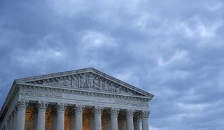 In this Sunday, May 3, 2020 photo, clouds roll over the Supreme Court at dusk on Capitol Hill in Washington. On Monday, May 4, the Supreme Court for the first time audio of court's arguments will be heard live by the world and the first arguments by telephone. (AP Photo/Patrick Semansky)