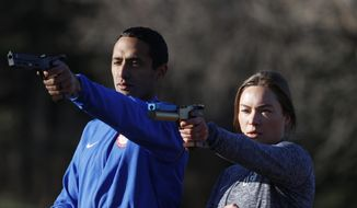USA Olympic modern pentathlon team members Amro ElGeziry and his wife, Isabella Isaksen practice shooting at targets in a park in Colorado Springs, Colo., Friday, April 24, 2020. Amro Elgeziry and Isabella Isaksen are just your ordinary married Olympic modern pentathlon couple trying to navigate their way through the challenges of training during the coronavirus pandemic. Their sport consists of five events, but they can't practice equestrian horse jumping or swimming at the moment with the facilities closed. For the rest, they improvise. They practice their fencing footwork in the backyard, shoot laser pistols at a target in a nearby park and squeeze in early morning runs along trails as they train for the Tokyo Games in 2021. (AP Photo/David Zalubowski) **FILE**