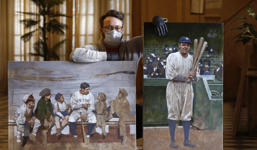 "In this Wednesday, April 29, 2020, photo, Brooklyn-based baseball artist Graig Kreindler poses with two of his paintings of Babe Ruth, both unfinished, in the lobby of his residence in New York. Over 200 of Kreindler's paintings form the bulk of the exhibit ""Black Baseball in Living Color:The Art of Graig Kreindler,"" at the Negro Leagues Baseball Museum in Kansas City, Mo. The museum is closed now, but expects to reopen early in June. Both paintings of Ruth are based on photographs. (AP Photo/Kathy Willens)"