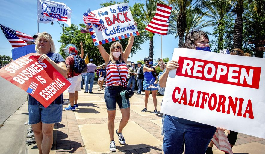 Protesters hold signs during a rally against California's stay-at-home orders that were put in place due to the coronavirus outbreak, in Rancho Cucamonga, Calif., Sunday, May 3, 2020. (Watchara Phomicinda/The Orange County Register via AP)