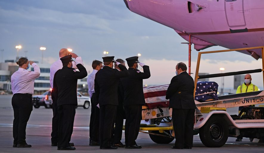 Ambulnz paramedics and Aurora firefighters salute as the casket carrying the body of paramedic Paul Cary is removed from a plane at Denver International Airport on Sunday, May 3, 2020, in Denver. Cary died from coronavirus after volunteering to help combat the pandemic in New York City. (Helen H. Richardson/The Denver Post via AP, Pool)