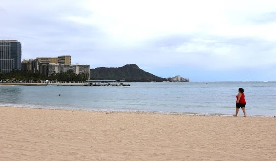 In this April 21, 2020, photo, a woman walks on Waikiki Beach in Honolulu. Hawaii has some of the lowest coronavirus infection and mortality rates in the U.S. (AP Photo/Caleb Jones)  **FILE**