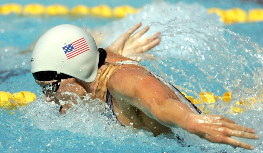 In this Aug. 14, 2004, file photo, Jenny Thompson swims during a qualifying heat of the 100 meter butterfly at the Olympic Aquatic Centre during the 2004 Olympic Games in Athens. One of America's greatest Olympic swimmers, Thompson is now on the front line of the fight against coronavirus as an anesthesiologist at the VA hospital in Charleston, South Carolina. (AP Photo/Mark J. Terrill, File)  **FILE**