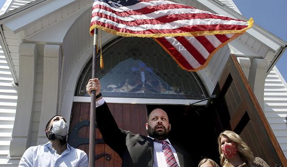 Adams Sq. Baptist Church Pastor Kris Casey waves an American flag after opening his church doors for Sunday service on May 3, 2020 in Worcester, Mass. (Nancy Lane/The Boston Herald via AP)