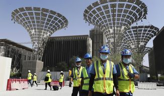 In this Oct. 8, 2019, file photo, technicians walk at the under a construction site of the Expo 2020 in Dubai, United Arab Emirates. Dubai's Expo 2020 world's fair will be postponed to Oct. 1, 2021, over the new coronavirus pandemic, a Paris-based body behind the events said Monday, May 4, 2020. (AP Photo/Kamran Jebreili, File)