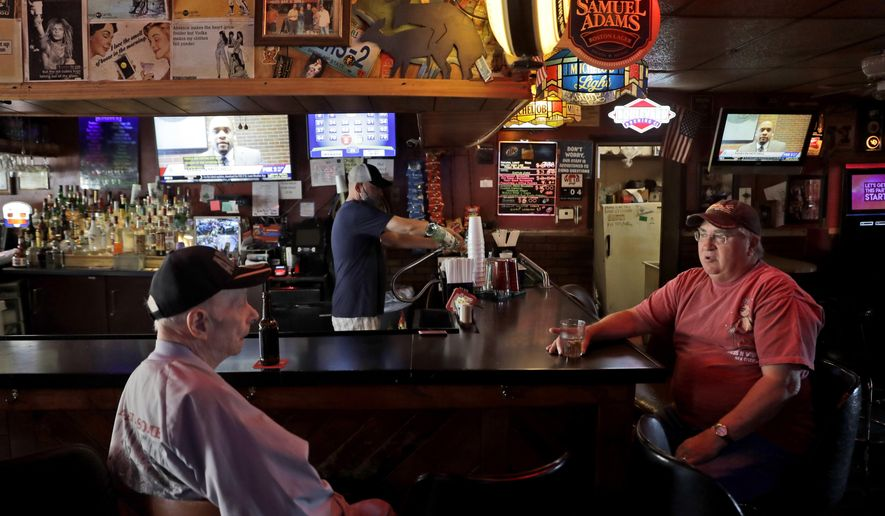 Bartender Greg Anderson, center, pours drinks as customers Rudy Leftholz and Ray Nash, left, chat on the first day Tuner's Bar and Grill has reopened after being closed in an effort to slow the spread of the coronavirus Monday, May 4, 2020, in St. Charles, Mo. Business in some parts of Missouri, including St. Charles, have been allowed to reopen on Monday after the state's stay-at-home order expired. (AP Photo/Jeff Roberson)