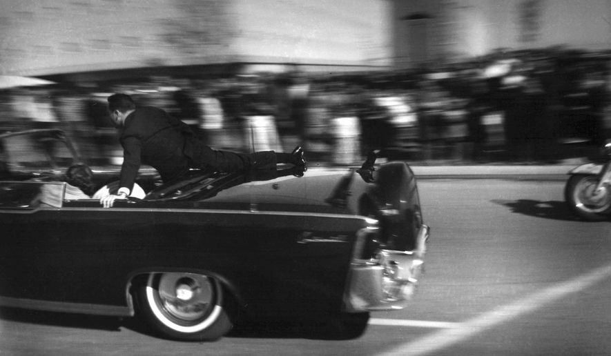 FILE - In this Nov. 22, 1963 file photo, the limousine carrying mortally wounded President John F. Kennedy races toward the hospital seconds after he was shot in Dallas. Secret Service agent Clinton Hill is riding on the back of the car, Nellie Connally, wife of Texas Gov. John Connally, bends over her wounded husband, and first lady Jacqueline Kennedy leans over the president. (AP Photo/Justin Newman, File)