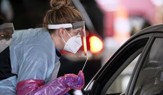 A nurse at a drive-thru location in Omaha, Neb., holds a swab as she prepares to administer a test for the coronavirus, Monday, May 4, 2020. Nebraska is ramping up testing for the virus as part of the TestNebraska initiative.(AP Photo/Nati Harnik)
