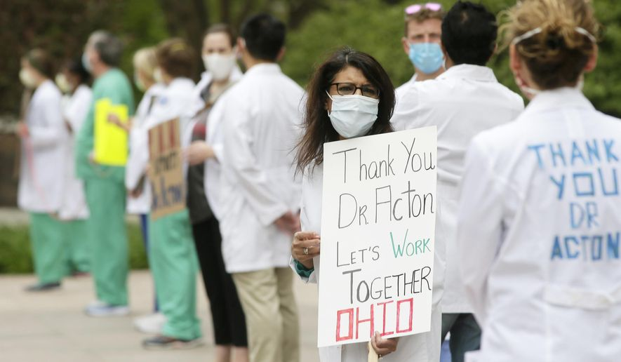 Dozens don masks along with scrubs and white coats as the Physicians Action Network held a public rally in support of Dr. Amy Acton at the Ohio Statehouse in downtown Columbus, Ohio, Sunday, May 3, 2020. The rally was a response to protesters of the state's stay-at-home orders who demonstrated outside Acton's home in Bexley on Saturday. (Barbara J. Perenic/The Columbus Dispatch via AP)