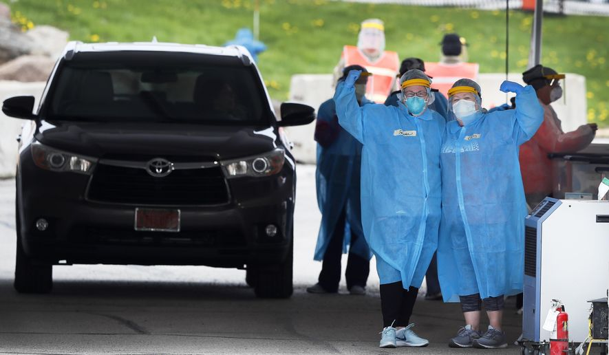 In this Friday, May 1, 2020, photo, medical workers flex their muscles as they pose for a photo at a drive-thru COVID-19 testing site in Waterloo, Iowa. (AP Photo/Charlie Neibergall)