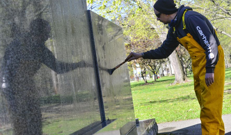 Tony Lebron, maintenance worker for the Brattleboro Recreation Department, paints on a compound that helps remove spray paint while cleaning up a war memorial on the Commons, in Brattleboro, Vt., on Monday, May 4, 2020.  (Kristopher Radder/The Brattleboro Reformer via AP)