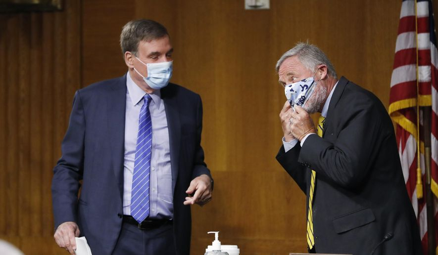 Senate Intelligence Committee Chairman Sen. Richard Burr, R-N.C. right, adjusts his mask while talking to Vice Chairman Sen. Mark Warner, D-Va., at the conclusion of a nomination hearing to consider Rep. John Ratcliffe, R-Texas, to be Director of National Intelligence, on Capitol Hill in Washington, Tuesday, May. 5, 2020. (AP Photo/Andrew Harnik, Pool)  **FILE**