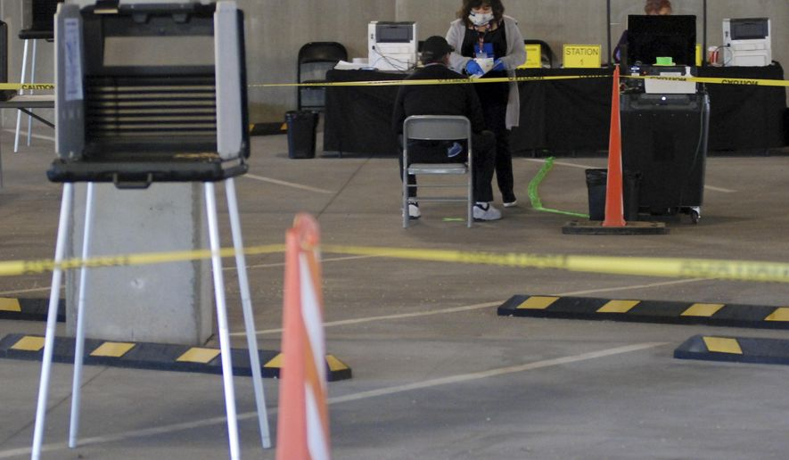 Election workers attend to voters at a makeshift polling station inside a parking garage in Santa Fe, N.M., on Tuesday, May 5, 2020. The arrangements by Santa Fe County Clerk Geraldine Salazar allow for greater social distancing and air circulation to guard against transmission of the coronavirus and avoids possible contamination of Santa Fe County government offices. Early in-person voting in New Mexico's June 2 primary began as election authorities encourage absentee balloting by mail. (AP Photo/Morgan Lee)