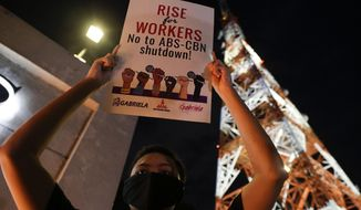 An activist holds a slogan outside the headquarters of broadcast network ABS-CBN corp. on Tuesday, May 5, 2020 in Quezon city, Metro Manila, Philippines. A Philippine government agency has ordered the country's leading broadcast network, which the president has targeted for it's critical news coverage, to halt operations after its congressional franchise expired, sparking shock over the loss of a major news provider during the coronavirus pandemic. (AP Photo/Aaron Favila)