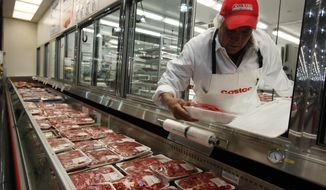 In this Dec. 8, 2009 file photo, a butcher places beef on display at Costco in Mountain View, Calif. U.S. meat supplies are dwindling due to coronavirus-related production shutdowns. As a result, some stores like Costco and restaurants like Wendy's are limiting sales. U.S. beef and pork processing capacity is down 40% from last year. On Monday, May 4, 2020 nearly 20% of U.S. Costco, Sam's Club, Hy-Vee and Kroger are limiting purchases of meat to avoid panic buying. (AP Photo/Paul Sakuma, file)