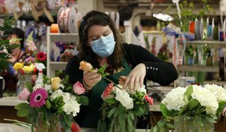 Tara Van Wieren works on a Mother's Day flower arraignment at Relles Florist in Sacramento, Calif., Tuesday, May 5, 2020. Florists are among the retail businesses that Gov. Gavin Newsom said might be eligible to open before the end of this week under upcoming state guidelines concerning the coronavirus. (AP Photo/Rich Pedroncelli)