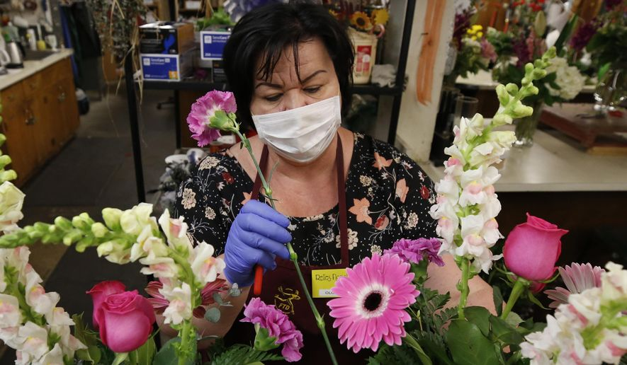 Olga Karamalak puts the finishing touches on a Mother's Day flower arraignment at Relles Florist in Sacramento, Calif., Tuesday, May 5, 2020. Florists are among the retail businesses that Gov. Gavin Newsom said might be eligible to open before the end of this week under upcoming state guidelines on the coronavirus. (AP Photo/Rich Pedroncelli)