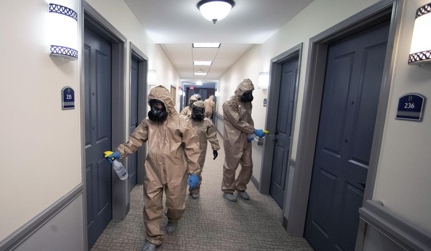 Members of the Georgia National Guard work to clean and disinfect hallways and common areas at Provident Village assisted living and memory care home Tuesday, May 5, 2020, in Smyrna, Ga. Despite having no cases among residents or staff the home welcomed the extra help from the guard. (AP Photo/John Bazemore)