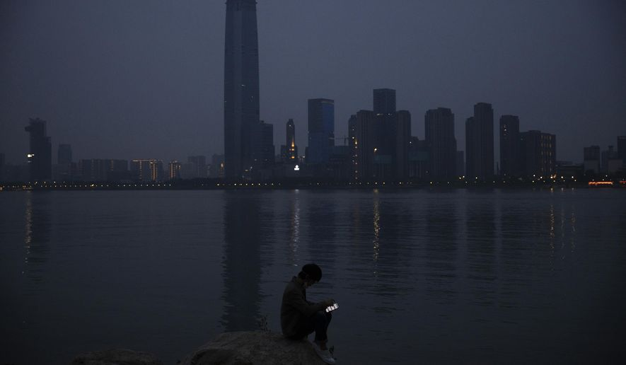 In this April 5, 2020, file photo, a man checks his mobile phone along the Yangtze River in Wuhan in central China's Hubei province. As governments around the world consider how to monitor new coronavirus outbreaks while reopening their societies, many are starting to bet on smartphone apps to help stanch the pandemic. (AP Photo/Ng Han Guan, File)