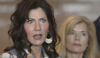 FILE - In this March 18, 2020 file photo, South Dakota Gov. Kristi Noem, left, updates media on the COVID-19 pandemic during a news conference at Monument Health in Rapid City, S.D. While many other governor's have broken from President Donald Trump on stay-at-home orders to curb the spread of coronavirus or when to restart economic activity, Noem has tracked close to the president.  (Jeff Easton/Rapid City Journal via AP, File)