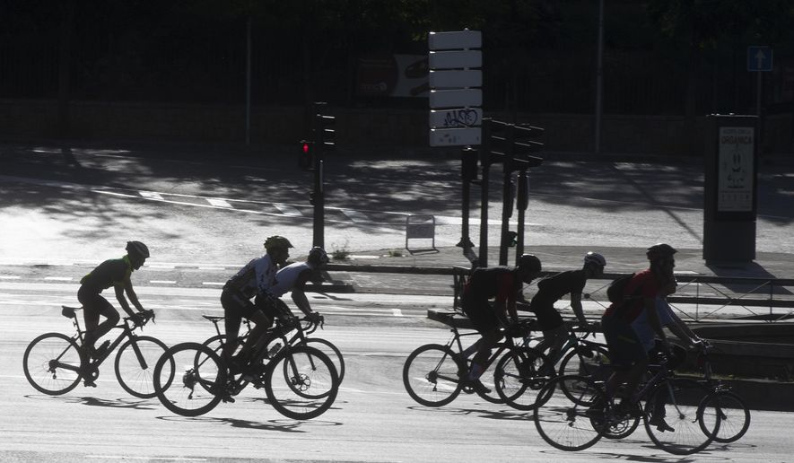 In this photo taken on Sunday May 3, 2020, a group of cyclists, many on racing bikes, ride down the Paseo de la Castellana boulevard in Madrid, Spain after Spaniards were able to go outdoors to do exercise for the second time in seven weeks since the lockdown began to battle the coronavirus outbreak. High-performance athletes were allowed to resume training this week but some reported being harassed by local residents who thought they were breaking confinement rules. (AP Photo/Paul White) ** FILE **