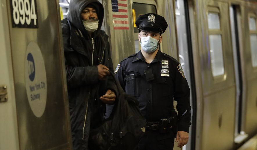 A man is removed from a train by a New York Police officer at the Coney Island Stillwell Avenue Terminal, Wednesday, May 6, 2020, in the Brooklyn borough of New York. (AP Photo/Frank Franklin II)