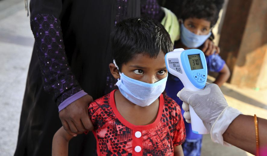 An Indian health worker checks the temperature of a child who had been stranded for weeks due to the lockdown to curb the spread of new coronavirus before allowing her to board a bus, in Bangalore, India, Wednesday, May 6, 2020. India partly relaxed its lockdown this week. (AP Photo/Aijaz Rahi)