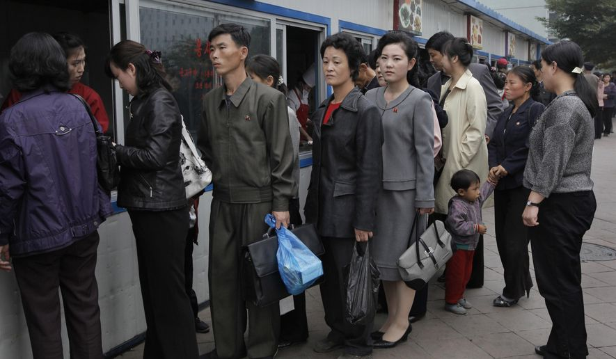 FILE- In this Oct. 11, 2010, file photo, residents queue up at a store to buy food in Pyongyang, North Korea. The coronavirus pandemic appears to be taking a heavy toll on North Korea, forcing its leader Kim Jong Un to sharply shrink his public activities and his people to go on panic buying of daily necessities, South Korea's spy agency told lawmaker Wednesday, May 6, 2020. (AP Photo/Vincent Yu, File)