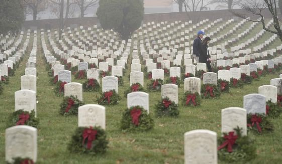 In this Dec. 14, 2019, file photo, people walk among headstones with holiday wreaths in Arlington National Cemetery during Wreaths Across America Day in Arlington, Va. (AP Photo/Sait Serkan Gurbuz, File)