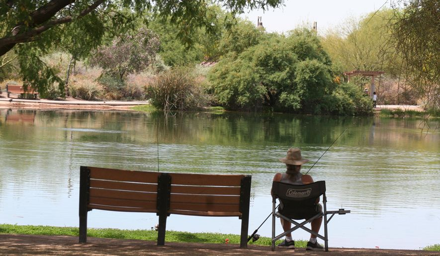 In this April 30, 2020 photo, a fisherman watches his line from the shade at Veterans Oasis Park in Chandler, Ariz. People who have been locked down during the coronavirus have been turning to fishing at community lakes as a chance to go outdoors and still following social-distancing guidelines. (AP Photo/John Marshall)  **FILE**
