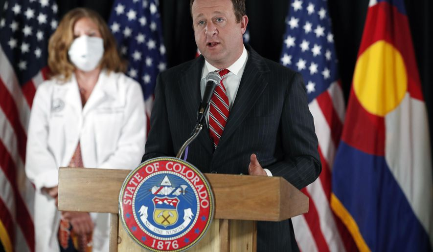 Colorado Governor Jared Polis, right, makes a point as nurse Laura Rosenthal of the University of Colorado Medical School looks on during a news conference to update reporters on the state's efforts to stem the rise of the new coronavirus Wednesday, May 6, 2020, in Denver. (AP Photo/David Zalubowski) **FILE**